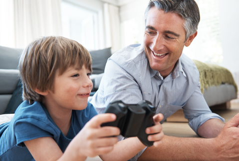Father watching son play video game with a bluetooth controller